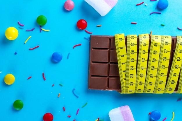 Schokolade wird in ein maßband mit verschiedenen süßigkeiten eingewickelt