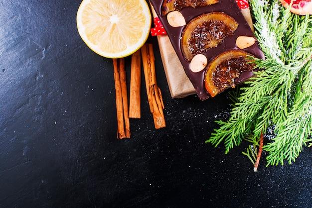 Schokolade, zitrone, granatapfel und zimt auf schwarzem