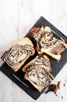 Schokoladen-babka oder brioche-brot. hausgemachtes süßes wüstengebäck - schokoladenwirbelbrot mit marmorstruktur. geschnitten auf weißem hintergrund