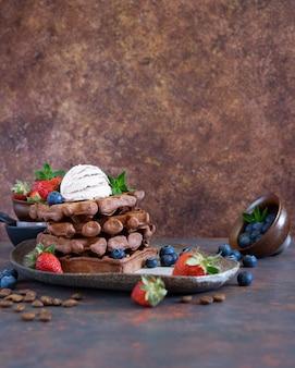 Schokoladen-belgische waffeln mit frischen beeren und kaffeeeis auf einer keramischen platte auf brauner tabelle