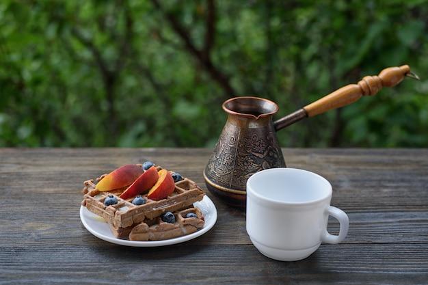 Schokoladen-belgische waffeln mit früchten, tasse kaffee und ceezve