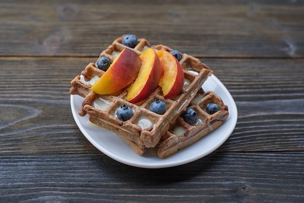 Schokoladen-belgische waffeln mit früchten und beeren. leckeres frühstück. nahansicht