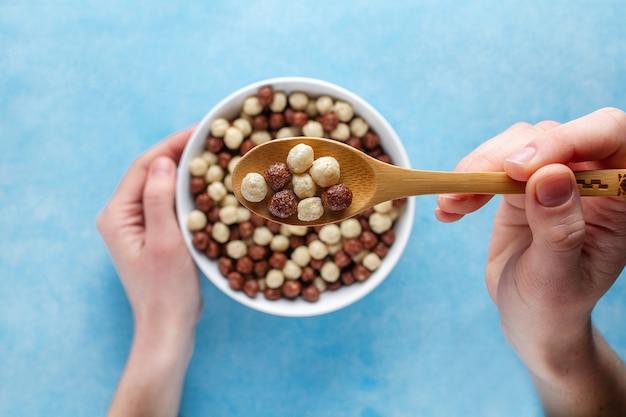 Schokoladen-, braune und weiße, glasierte kugeln für trockenes gesundes frühstück. ansicht von oben. getreidelöffel und -schüssel in den händen auf einer blauen brandung