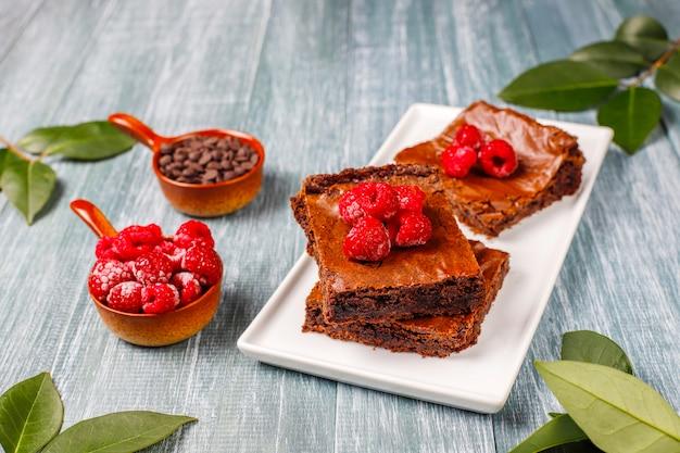 Schokoladen-brownie-kuchen-dessertscheiben mit himbeeren und gewürzen