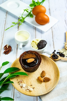 Schokoladen-brownie-kuchen in pappbechern dekoriert mit komponenten für die herstellung von kuchen auf holz