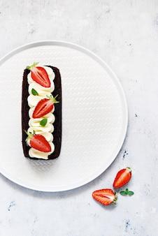 Schokoladen-brownie mit luftiger vanillecreme und frischen erdbeeren. schokoladenkuchen mit sahne und frischen beeren.