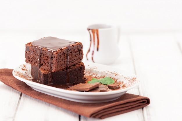Schokoladen-brownie-quadratstücke mit tadellosen blättern und kakaopulver