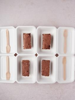 Schokoladen-brownie-scheiben in kartons mit holzgabel zum mitnehmen und liefern