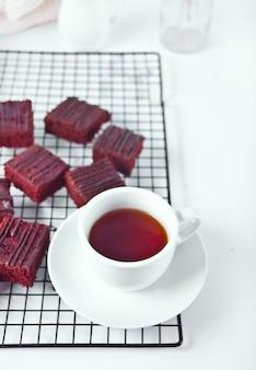Schokoladen-brownie und eine tasse tee auf dem träger.