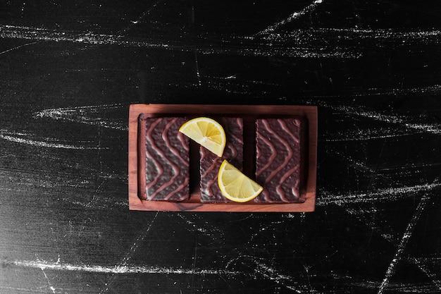 Schokoladen-brownies auf einem holzbrett mit zitronenscheiben.