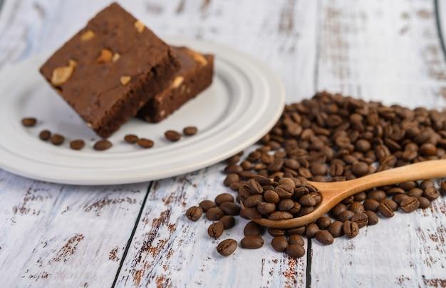 Schokoladen-brownies auf einem weißen teller und kaffeebohnen auf einem holzlöffel.