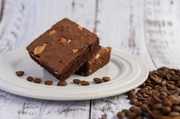 Schokoladen-brownies auf einem weißen teller und kaffeebohnen.
