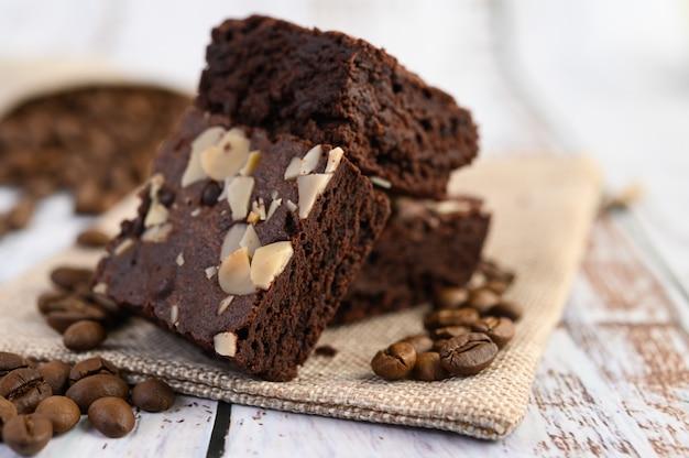Schokoladen-brownies auf sackleinen und kaffeebohnen auf einem holztisch.