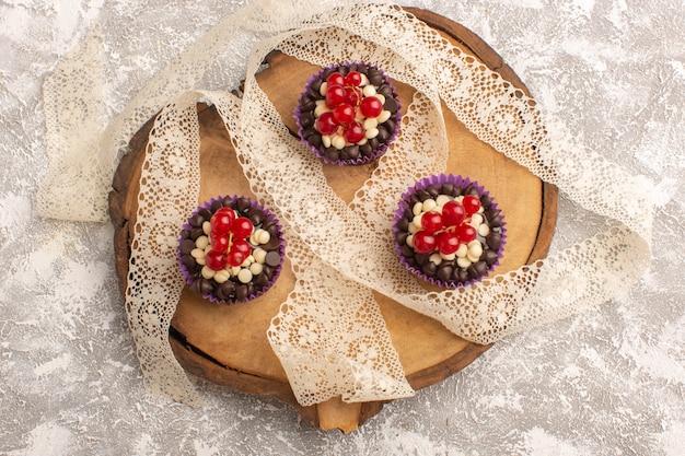 Schokoladen-brownies der draufsicht mit preiselbeeren auf dem süßen backteig des leichten schreibtischkuchens