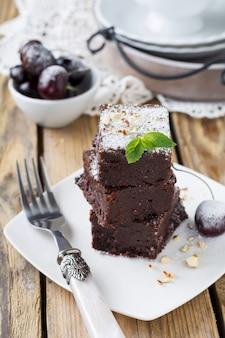 Schokoladen-brownies mit puderzucker und kirschen auf dunklem holz