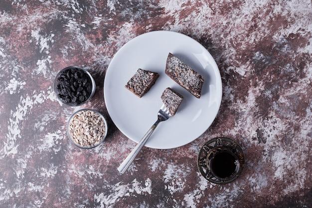 Schokoladen-brownies serviert mit einem glas tee, draufsicht