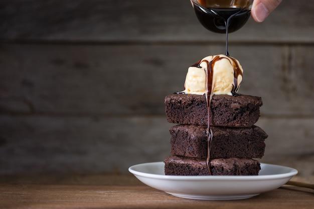 Schokoladen-brownies-stapel und vanilleeis auf der oberseite, aus holz