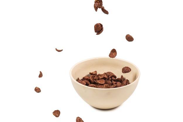 Schokoladen-cornflakes, die auf die weiße schüssel fallen, lokalisiert auf weiß. bewegung. copyspace.