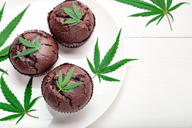 Schokoladen-cupcake-muffins mit cannabis verlässt unkraut cbd. medizinische marihuana-hanf-drogen im dessert. backen von unkrautmuffins mit marihuana auf weißem holztisch kochen. platz kopieren. ansicht von oben. nahansicht.