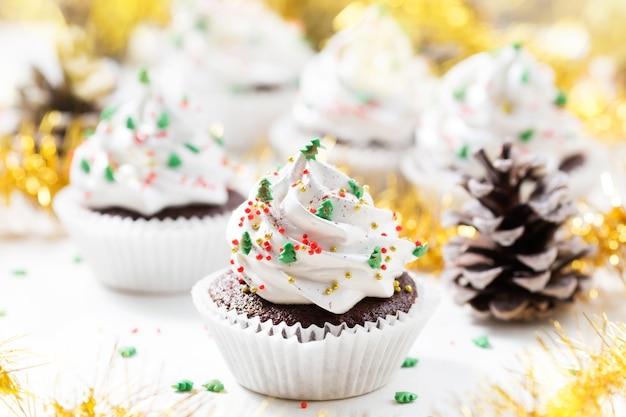 Schokoladen-cupcake verzierte weiße sahne- und tannenbäume. weihnachtssüßigkeiten.