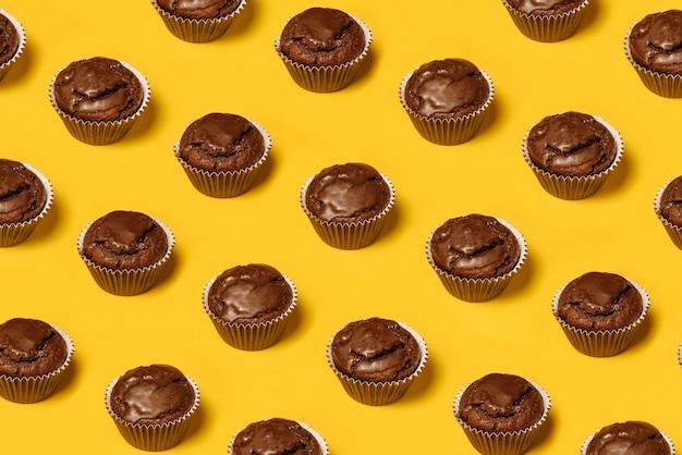 Schokoladen cupcakes oder kekse muster auf einem gelben hintergrund. sommer-minimalismus. isometrische flache lage. draufsicht. lebensmittelkonzept.