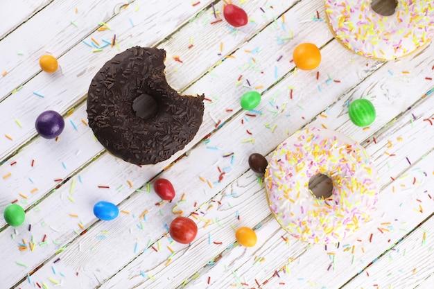 Schokoladen-donut auf weißem holzhintergrund und einer streuung von süßen ornamenten