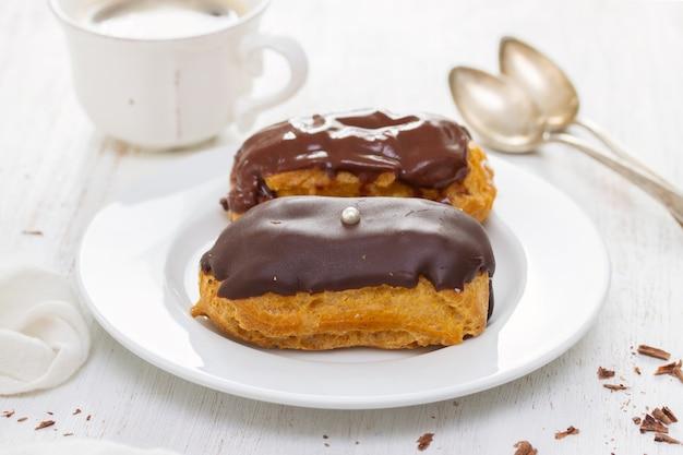 Schokoladen-eclairs auf weißer schale auf holzoberfläche