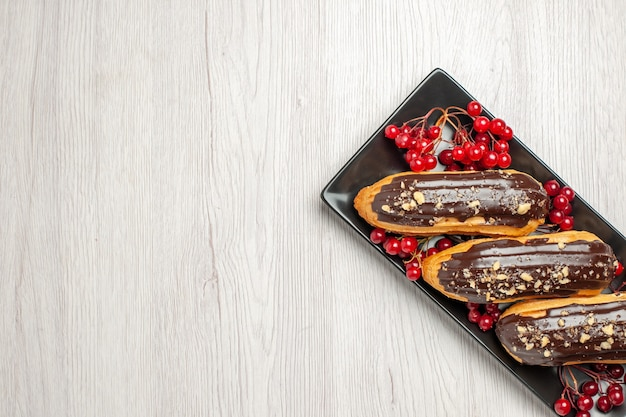 Schokoladen-eclairs und johannisbeeren in der oberen hälfte auf der schwarzen isometrischen rechteckigen platte auf der rechten seite des weißen holzbodens
