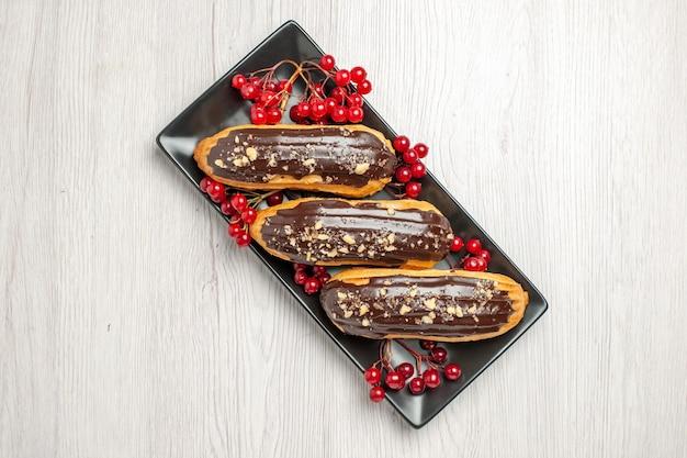Schokoladen-eclairs und johannisbeeren von oben auf dem schwarzen rechteckigen teller in der mitte des weißen holztischs