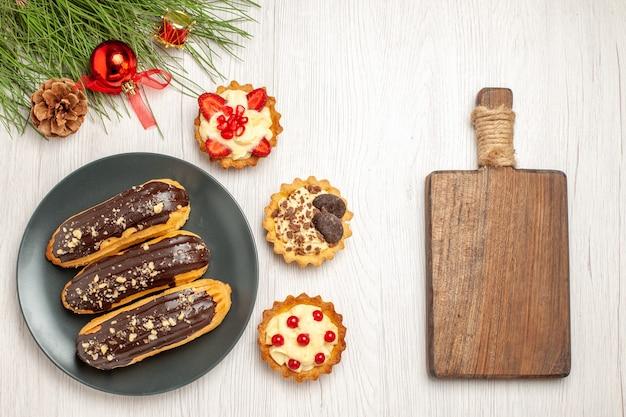Schokoladen-eclairs von oben auf dem grauen teller tört die kiefernblätter mit weihnachtsspielzeug links und einem schneidebrett rechts vom weißen holzboden