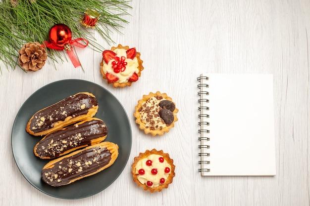 Schokoladen-eclairs von oben auf den grauen törtchen und den kiefernblättern mit weihnachtsspielzeug links und einem notizbuch rechts auf dem weißen holzboden