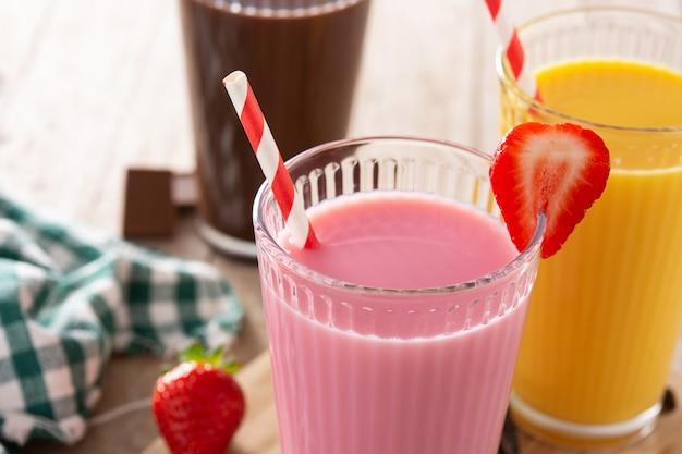 Schokoladen-, erdbeer- und vanillemilchshakes auf rustikalem holztisch