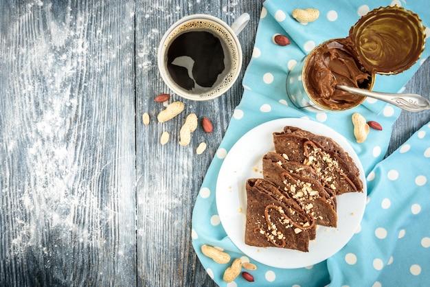 Schokoladen-hafer-pfannkuchen mit karamell und nüssen auf grauem holztisch.