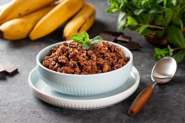 Schokoladen-haferflocken in weißer schüssel zum frühstück, horizontal