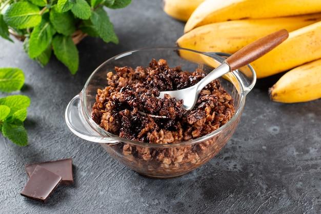 Schokoladen-haferflocken oder haferbrei mit schokolade darüber, serviert in einer kleinen schüssel (selective focus, focus in der mitte des breis)
