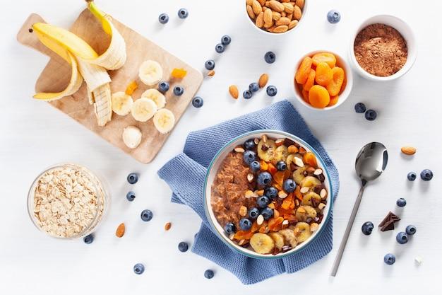 Schokoladen-haferflockenbrei mit blaubeeren, nüssen, bananen und getrockneten aprikosen für ein gesundes frühstück. draufsicht