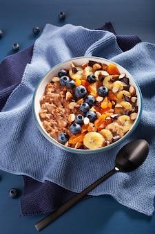 Schokoladen-haferflockenbrei mit blaubeeren, nüssen, bananen und getrockneten aprikosen für ein gesundes frühstück