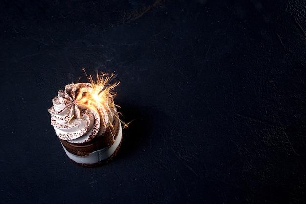 Schokoladen-himbeer-geburtstagstorte mit wunderkerze auf dunklem hintergrund