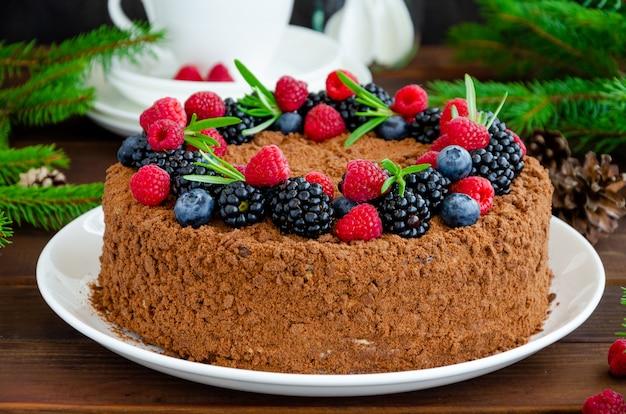Schokoladen-honig-kuchen mit sahne und frischen beeren auf einem weißen teller