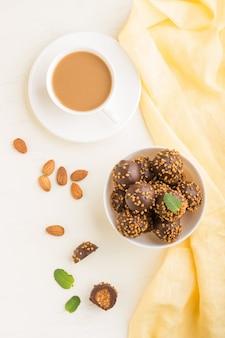 Schokoladen-karamellkugel-bonbons mit mandeln und einer tasse kaffee auf einer weißen holzoberfläche und gelbem textil