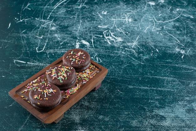 Schokoladen-keks-sandwiches mit streuseln auf holzbrett.