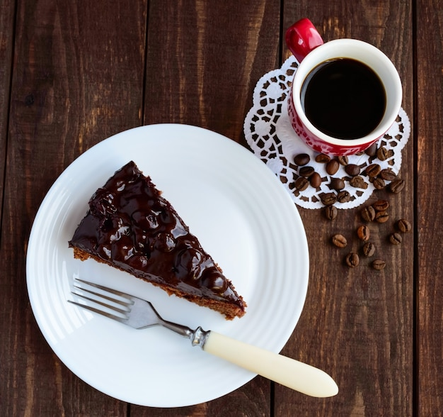 Schokoladen-kirsch-kuchen. ein stück auf einer weißen platte nahaufnahme. eine tasse kaffee. die draufsicht.