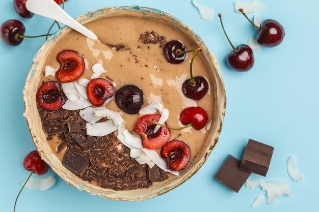Schokoladen-kirsch-smoothie-schüssel mit kokosnuss und bananen auf blauer oberfläche. gesundes veganes lebensmittelkonzept. roher veganer lebensstil.