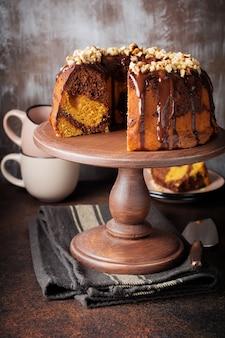 Schokoladen-kürbis-bundt-kuchen mit schokoladenglasur und walnuss auf dunkler betonoberfläche