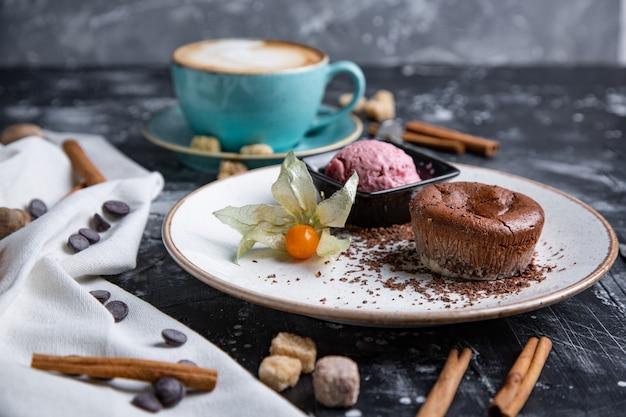 Schokoladen-lava-kuchen geschmolzen mit eis auf teller und cappuccino. eisbällchen in der tasse. dunkler schwarzer raum.