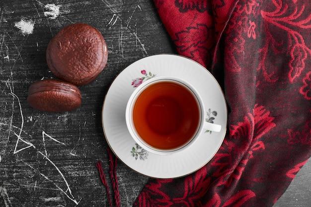 Schokoladen-marshmallow-kekse und eine tasse tee, draufsicht.