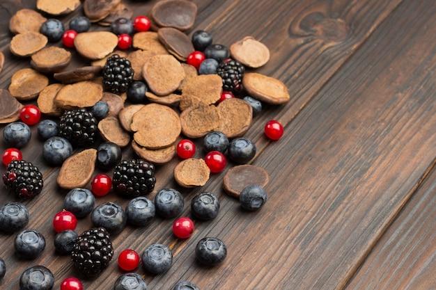 Schokoladen-mini-pfannkuchen und beeren, brombeeren, blaubeeren, rote johannisbeeren.
