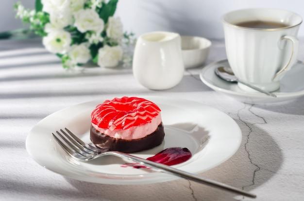 Schokoladen-minikuchen mit berri-marshmallow und gelee in teller und tasse kaffee in glastasse auf hellgrauem hintergrund, draufsicht. leckeres dessert. frühstückstisch gedeck.