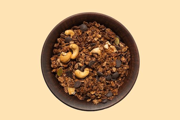 Schokoladen-müsli-getreide mit nüssen in einer schüsseloberfläche. isoliert auf weißem hintergrund.