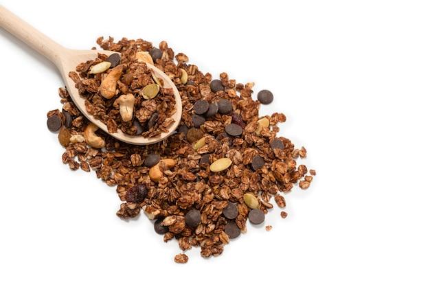 Schokoladen-müsli mit nüssen in einem holzlöffel. isoliert auf weißem hintergrund.